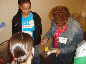 "Veronica R. Dowell of Twin Cedars Youth and Family Services works with her team to transport 12 plastic eggs across the room using only the tools provided during the ""Radioactive Eggs"" activity at the Best Practices in Youth Development training in 2012."